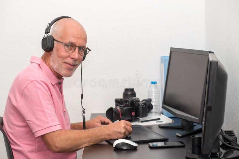 Rijpe mens die aan zijn grafiektablet werken royalty-vrije stock fotografie