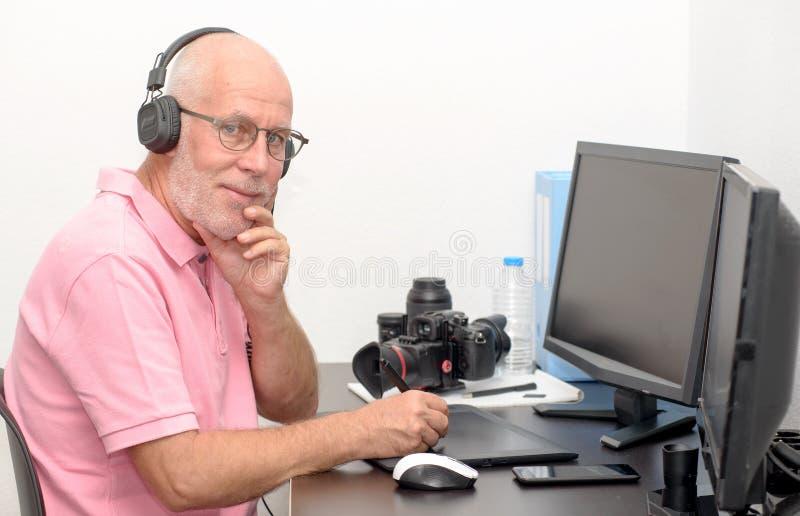 Rijpe mens die aan zijn grafiektablet werken royalty-vrije stock afbeelding