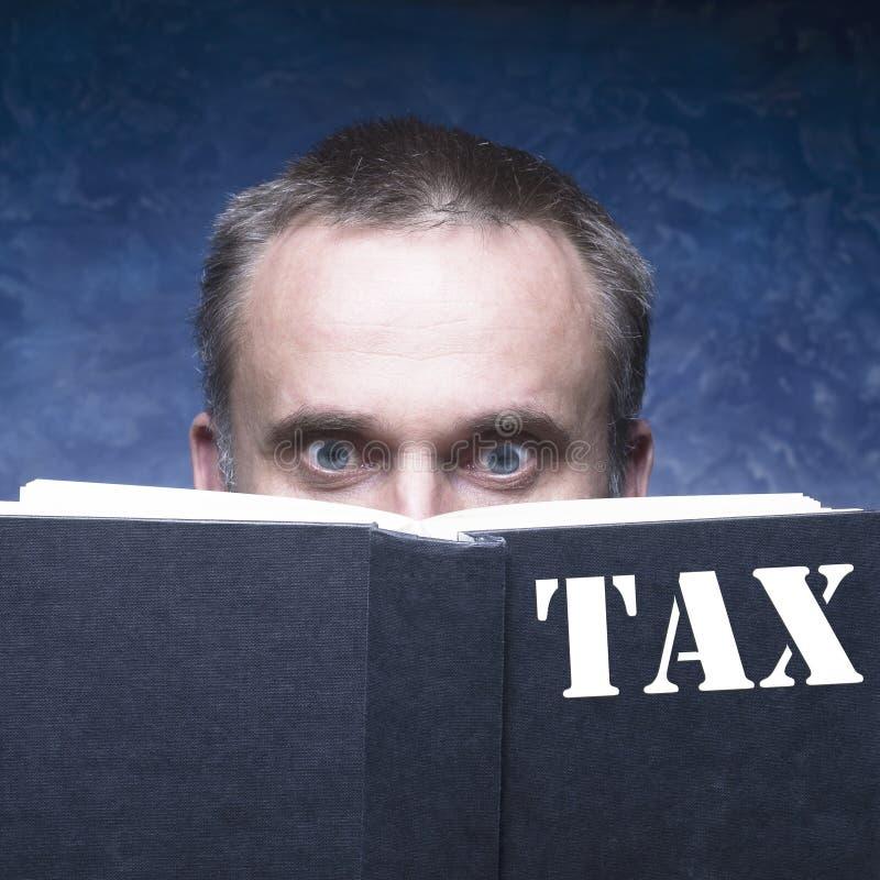 Rijpe mens die door boek over belasting worden geconcentreerd en wordt vastgehaakt stock afbeeldingen