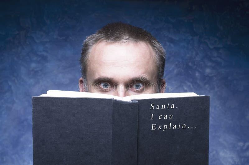 Rijpe mens die door boek worden geconcentreerd en wordt vastgehaakt Kerstman kan ik verklaren royalty-vrije stock afbeelding