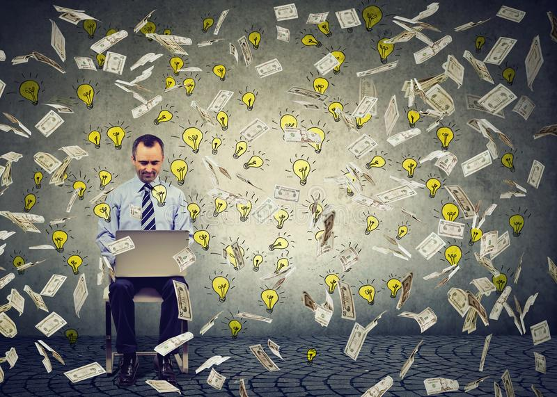 Rijpe mens die laptop met behulp van die online bedrijfsdollarrekeningen en gloeilampen bouwen die neer vallen stock foto's