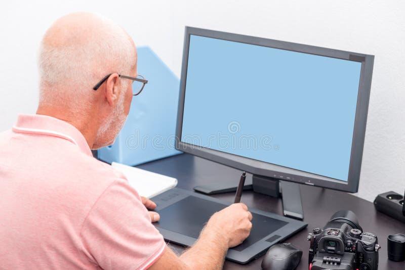 Rijpe mens die met grafiektablet werken in zijn bureau royalty-vrije stock fotografie