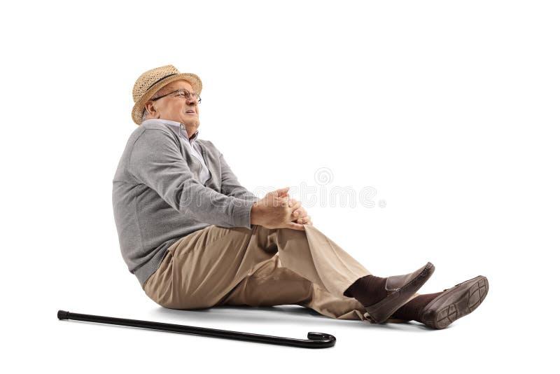 Rijpe mens die op de vloer liggen en zijn knie houden stock afbeelding