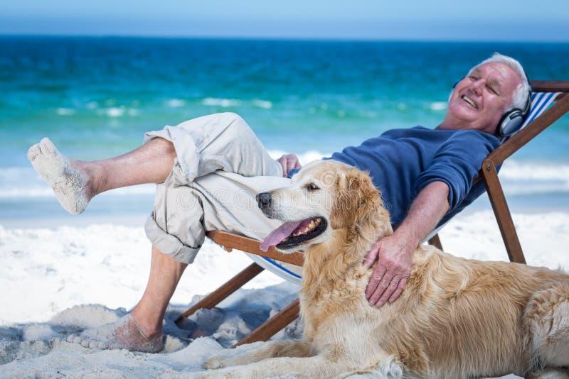 Rijpe mens die op een ligstoel rusten die aan muziek luisteren die zijn hond petting stock afbeelding