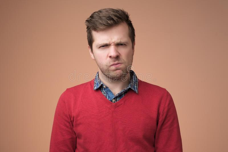 Rijpe mens die in rode sweater met ongeloofuitdrukking kijken stock foto