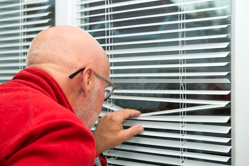 Rijpe mens die uit het venster kijken royalty-vrije stock afbeeldingen