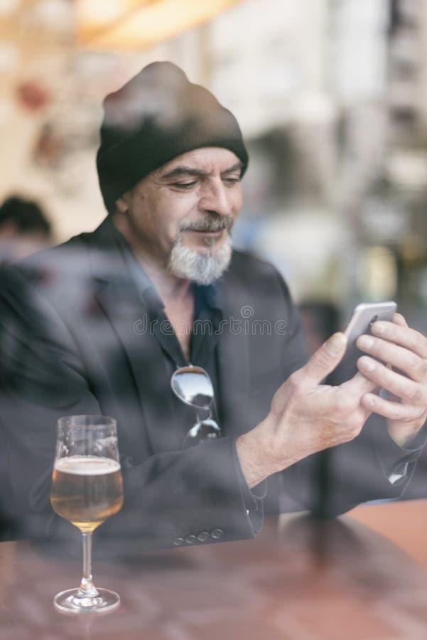 Rijpe mens in een koffie die van een ontspannend ogenblik genieten royalty-vrije stock afbeelding