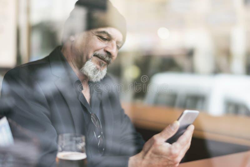 Rijpe mens in een koffie die van een ontspannend ogenblik genieten royalty-vrije stock fotografie