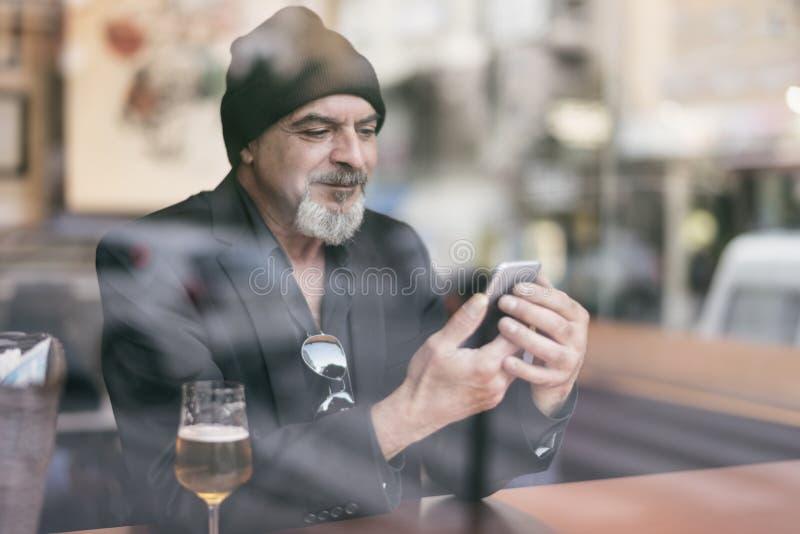 Rijpe mens in een koffie die van een ontspannend ogenblik genieten stock afbeelding