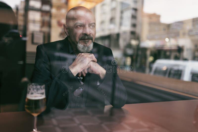Rijpe mens in een koffie die van een ontspannend ogenblik genieten stock afbeeldingen