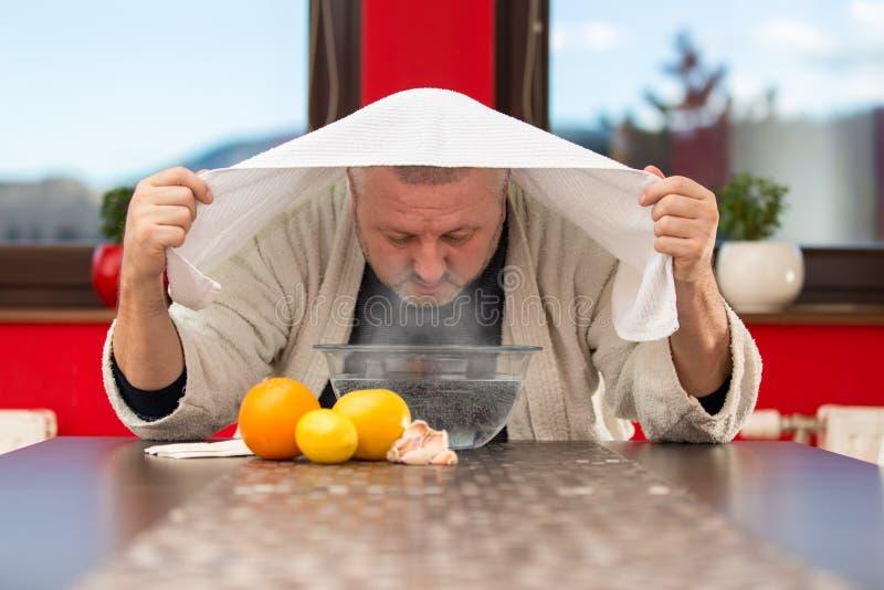 Rijpe mens met koude en griep Inhalatie van kruiden stock foto's