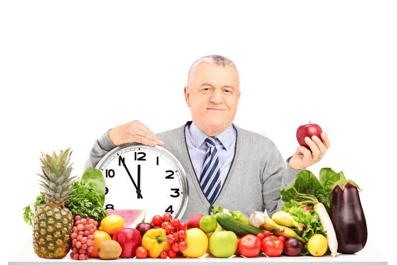 Rijpe mens met rode appel, klok en fruit en groenten stock foto