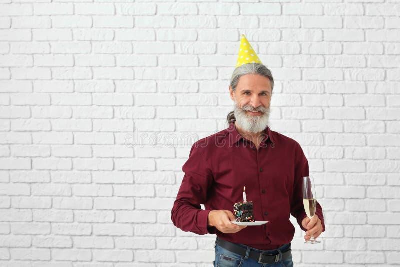 Rijpe mens met stuk van verjaardagscake en glas champagne op bakstenen muurachtergrond stock foto