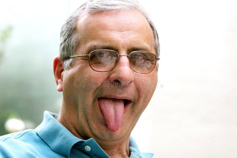 Rijpe mens met zijn uit tong stock foto