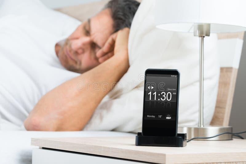Rijpe mens op bed met alarm op het cellphonescherm royalty-vrije stock afbeelding