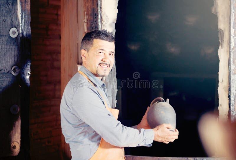Rijpe mensenpottenbakker die zwart verglaasd ceramisch schip naast ki houden royalty-vrije stock fotografie