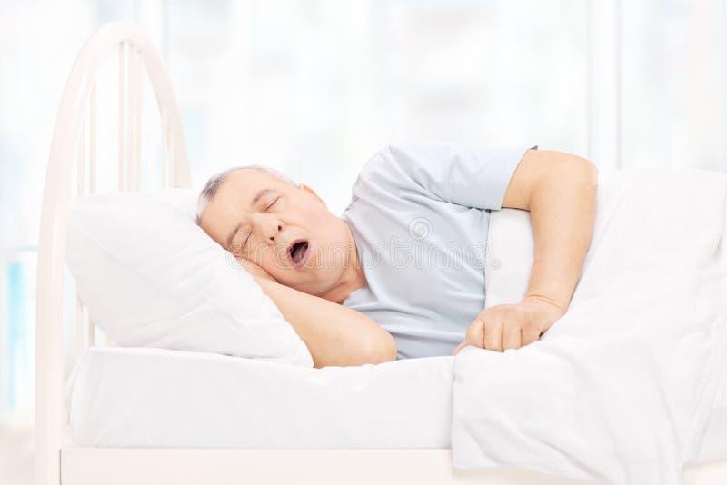 Rijpe mensenslaap in een comfortabel bed royalty-vrije stock foto