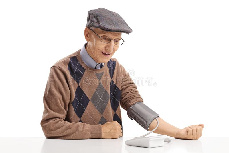 Rijpe mensenzitting bij een lijst en het meten van zijn bloeddruk royalty-vrije stock foto's