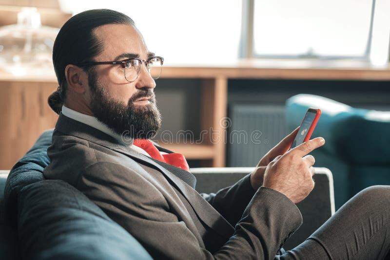 Rijpe modieuze zakenman die donker grijs kostuum en rode band dragen royalty-vrije stock foto