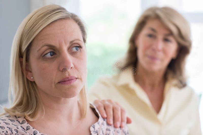 Rijpe Moeder Betrokken over Volwassen Dochter thuis stock afbeelding