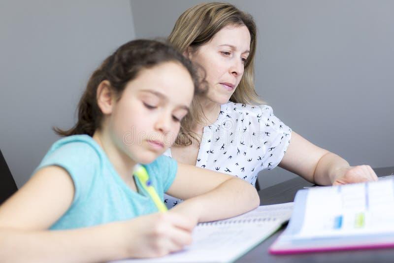 Rijpe moeder die haar kind met thuiswerk thuis helpen royalty-vrije stock afbeelding