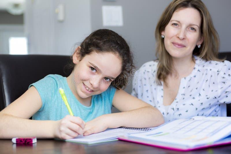 Rijpe moeder die haar kind met thuiswerk thuis helpen stock foto's