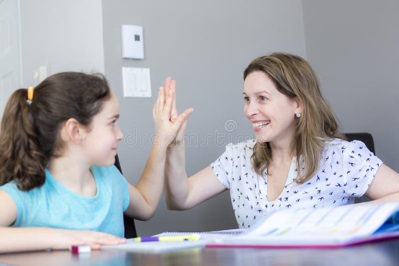 Rijpe moeder die haar kind met thuiswerk thuis helpen royalty-vrije stock afbeeldingen
