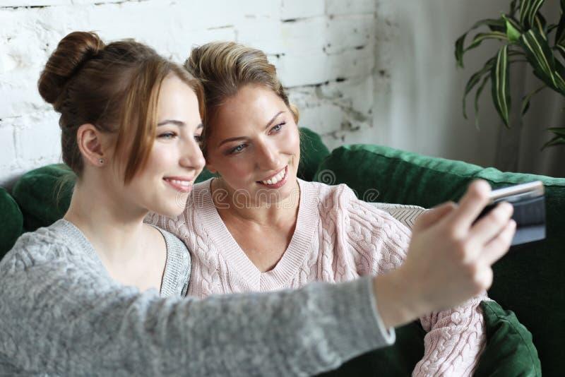 Rijpe moeder en haar dochter die een selfie maken die smartphone met behulp van royalty-vrije stock foto's