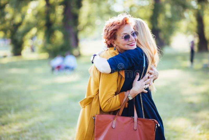 Rijpe moeder en volwassen dochter die in het park koesteren royalty-vrije stock foto