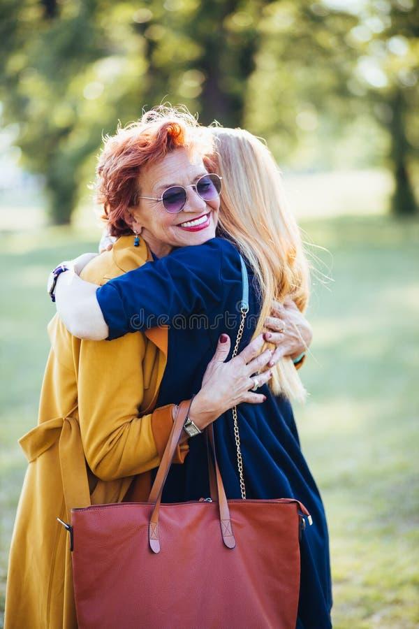 Rijpe moeder en volwassen dochter die in het park koesteren stock afbeelding