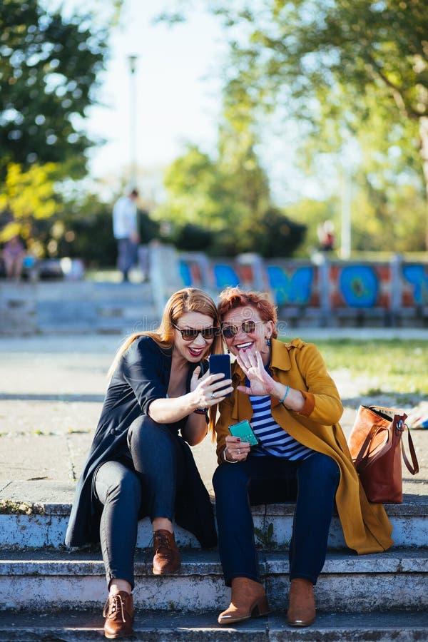 Rijpe moeder en volwassen dochter die selfie nemen stock foto