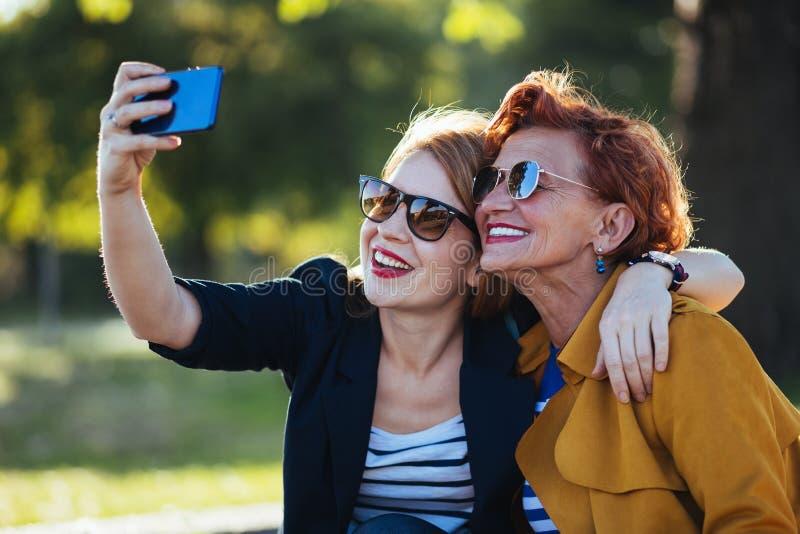 Rijpe moeder en volwassen dochter die selfie nemen stock foto's