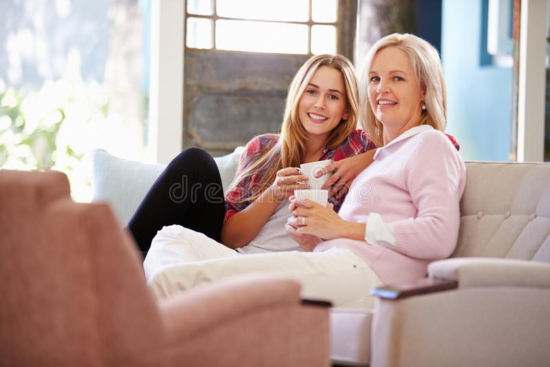 Rijpe Moeder met het Volwassen Dochter Ontspannen op Sofa At Home stock afbeeldingen
