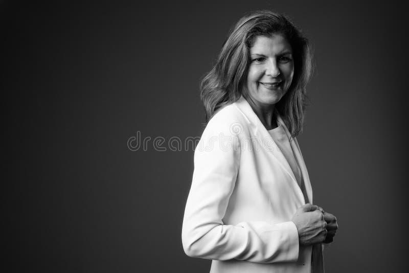 Rijpe mooie onderneemster tegen grijze achtergrond in zwarte royalty-vrije stock afbeeldingen