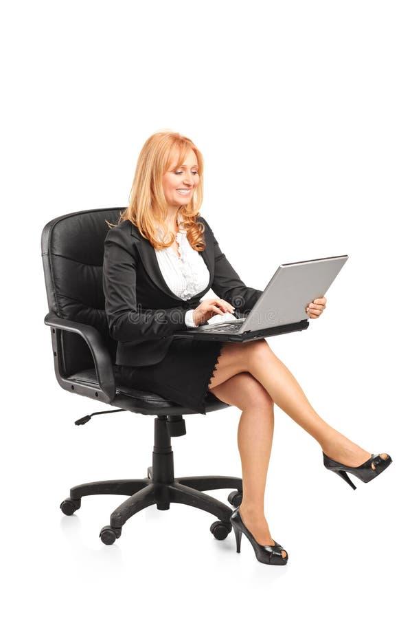 Rijpe onderneemster die aan laptop werken stock foto's