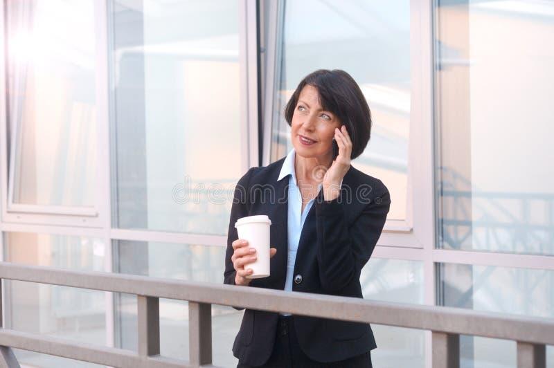 Rijpe onderneemster die een onderbreking voor een bureaugebouw hebben, die op de de telefoon en het drinken koffie spreken stock foto's