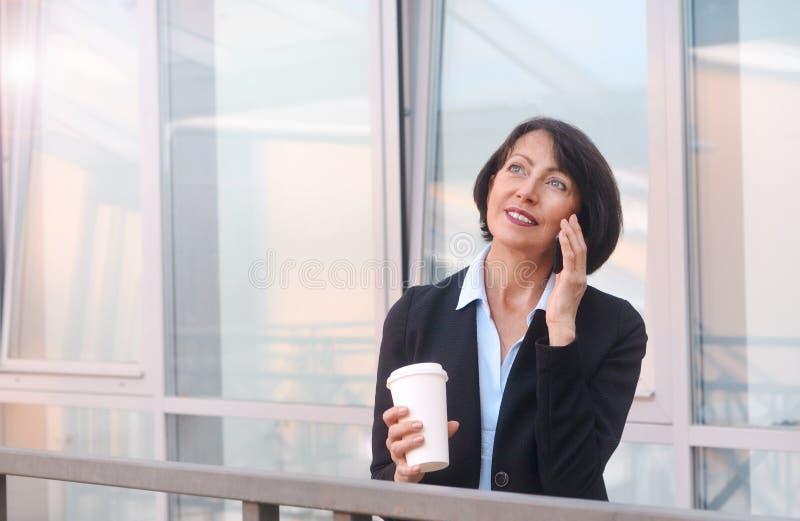 Rijpe onderneemster die een onderbreking voor een bureaugebouw hebben, die op de de telefoon en het drinken koffie spreken royalty-vrije stock foto's