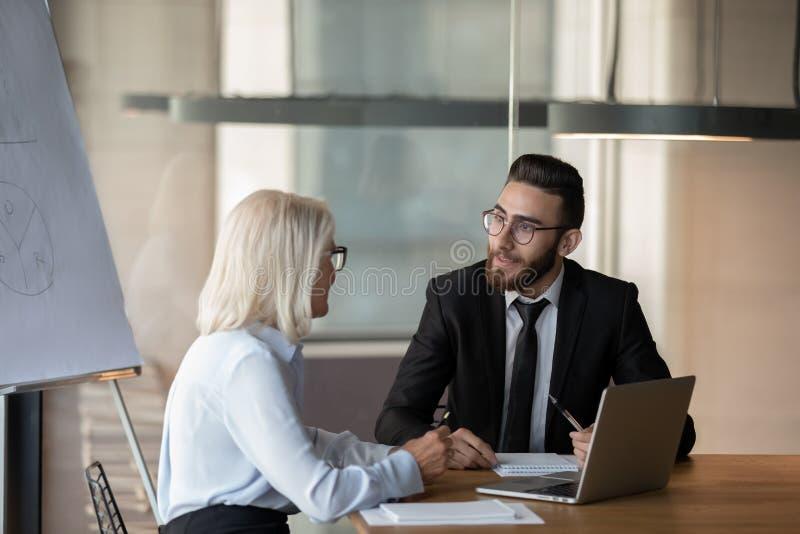 Rijpe onderneemster en zakenman die project in bestuurskamer bespreken royalty-vrije stock afbeeldingen
