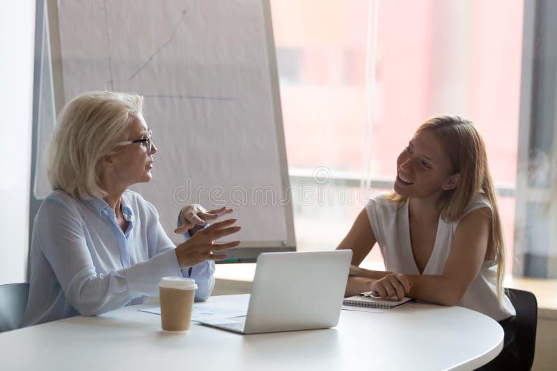 Rijpe onderneemstermentor die met vrouwelijke intern in bestuurskamer spreken stock foto