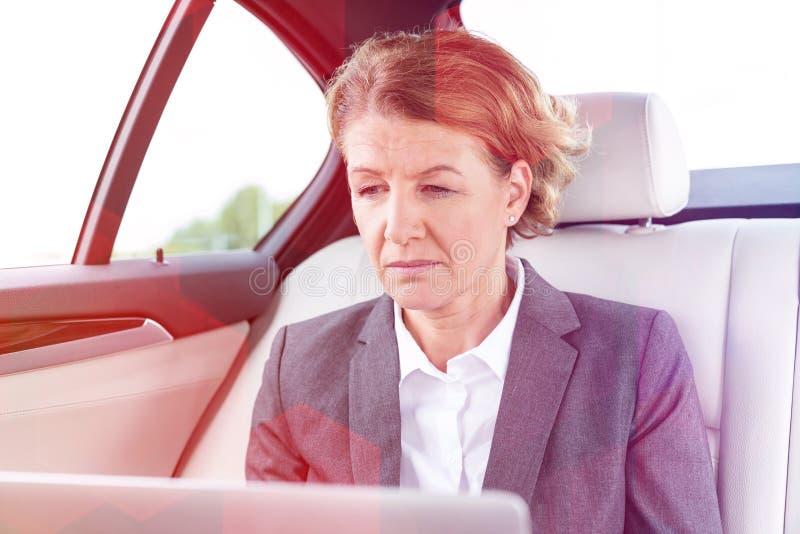 Rijpe onderneemsterzitting in auto tijdens reis stock foto