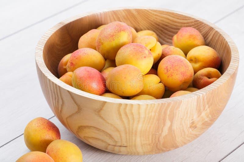 rijpe organische abrikozenvruchten in de houten kom van de asboom stock foto's