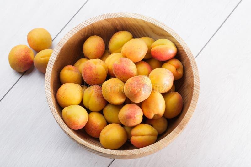 Rijpe organische abrikozenvruchten in de houten kom van de asboom stock afbeeldingen
