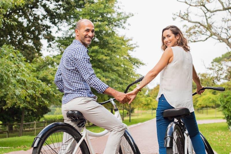 Rijpe paar berijdende fiets stock afbeelding
