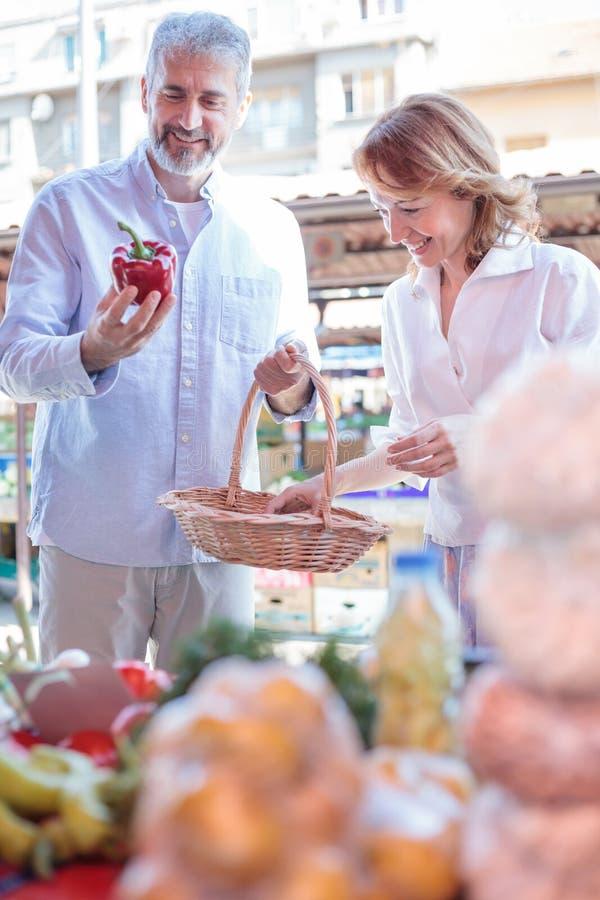 Rijpe paar het kopen groenten en kruidenierswinkels in een markt royalty-vrije stock afbeeldingen