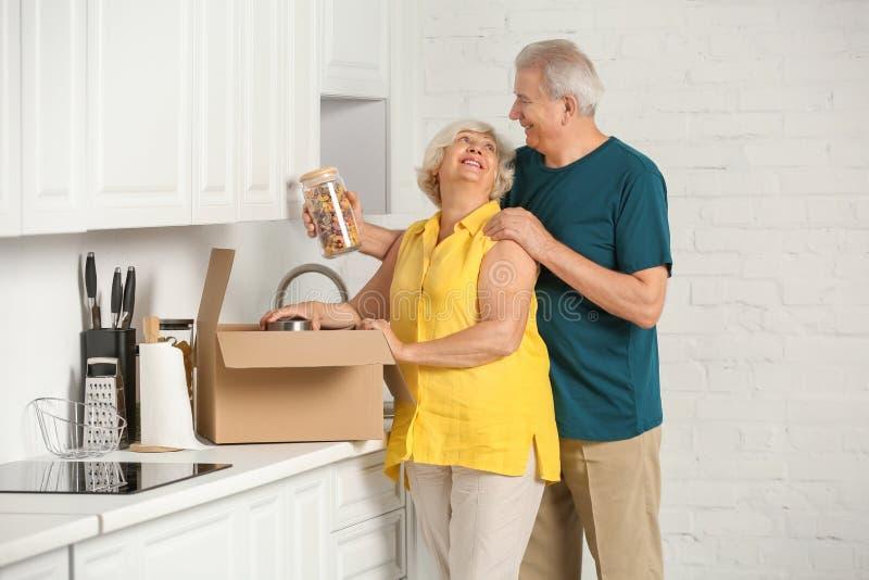 Rijpe paar uitpakkende bewegende doos met voedsel in keuken royalty-vrije stock foto