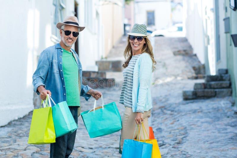 Rijpe paarholding het winkelen zakken op straat stock afbeeldingen