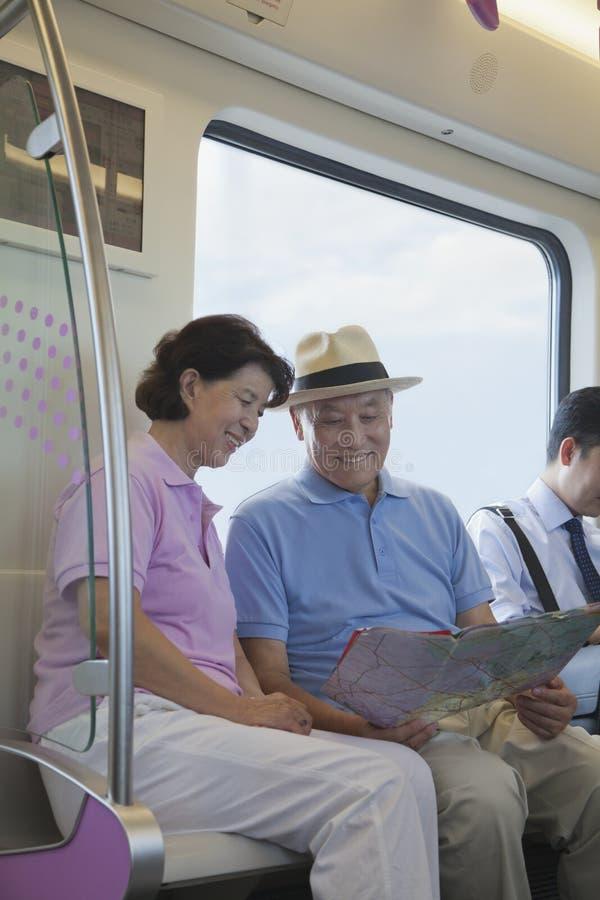 Rijpe paarzitting in de metro en het bekijken de kaart royalty-vrije stock afbeelding