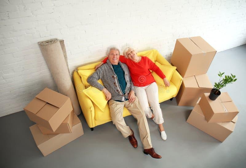 Rijpe paarzitting op bank dichtbij dozen na zich het bewegen in nieuw huis stock afbeelding