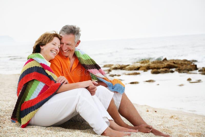 Rijpe paarzitting op het strand. royalty-vrije stock fotografie