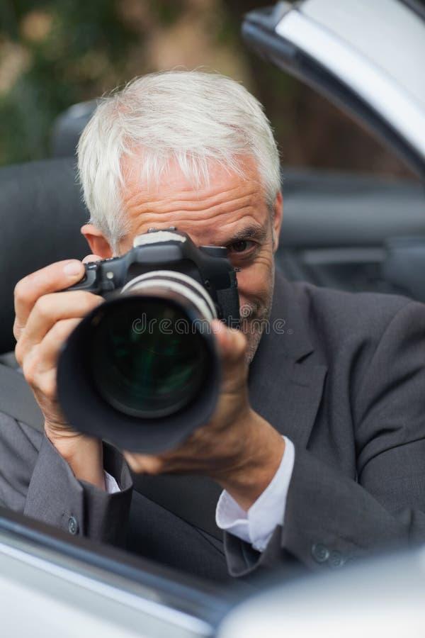 Rijpe paparazzi die beeld met professionele camera neemt royalty-vrije stock afbeelding